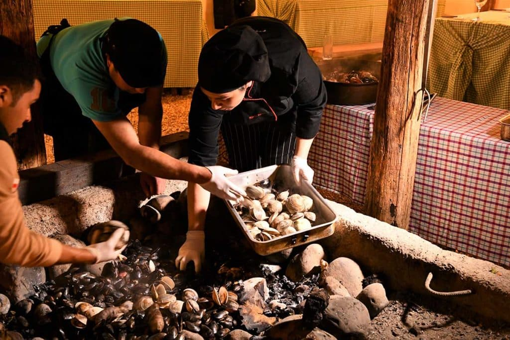 Chileans adding shellfish to the Curanto, Chiloe Island